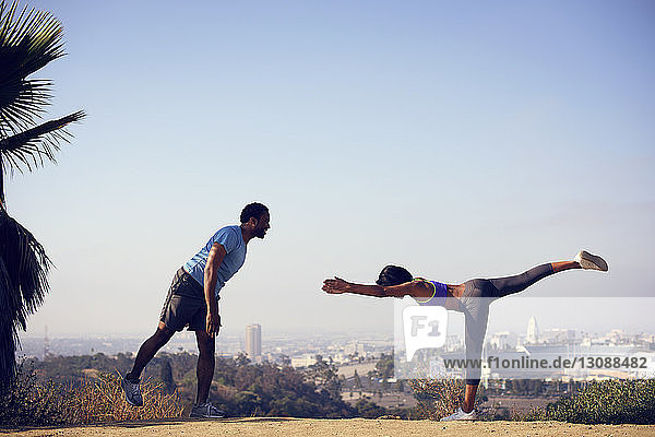 Mann und Frau trainieren auf einer Klippe vor klarem Himmel