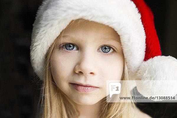 Portrait of cute girl in Santa hat against black background