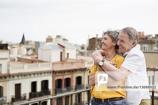 Cheerful senior couple looking at city view from terrace