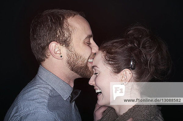 Side view of happy couple standing against black background