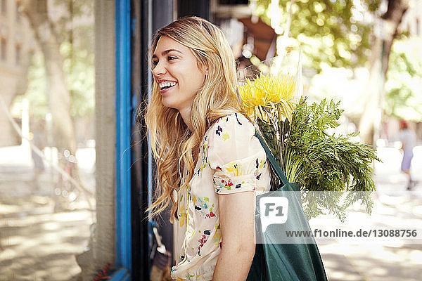 Lächelnde Frau mit Blumen steht am Glasfenster auf dem Bürgersteig