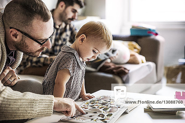 Father showing picture book to girl with partner sitting in background