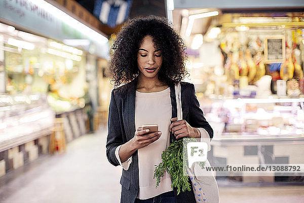 Frau benutzt Mobiltelefon beim Einkaufen auf dem Markt
