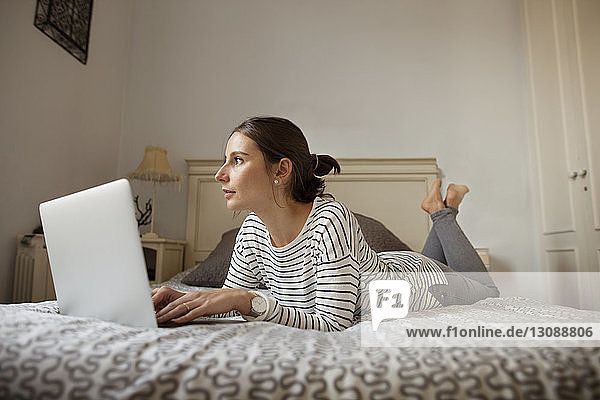 Thoughtful woman with laptop lying on bed at home