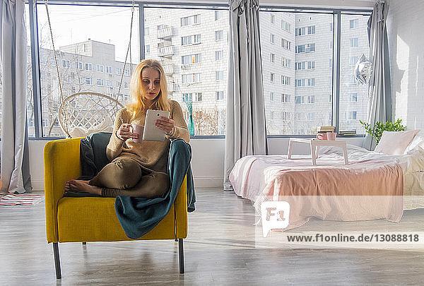 Frau benutzt Tablet-Computer  während sie zu Hause auf einem Sessel sitzt