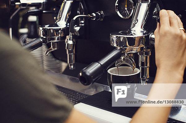 Ausgeschnittenes Bild eines Barista  der im Café Kaffee macht