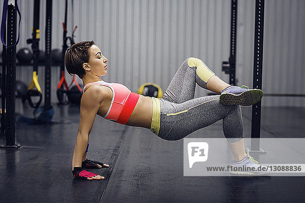 Side view of sporty woman exercising in gym