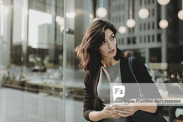 Frau schaut weg  während sie im Café ein Mobiltelefon benutzt