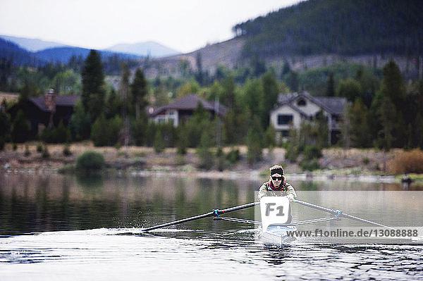Junge Frau beim Kajakfahren auf See gegen Berg