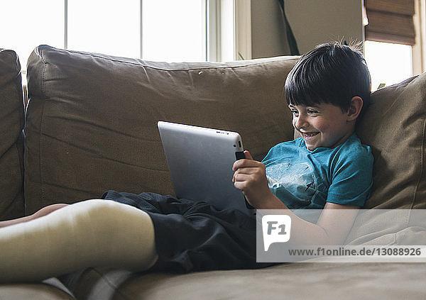 Lächelnder Junge mit gebrochenem Bein  der einen Tablet-Computer benutzt  während er zu Hause auf dem Sofa liegt