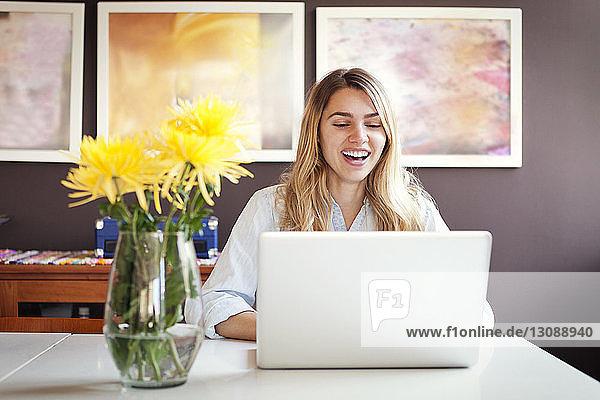 Fröhliche Frau mit Laptop und Vase auf dem Tisch zu Hause