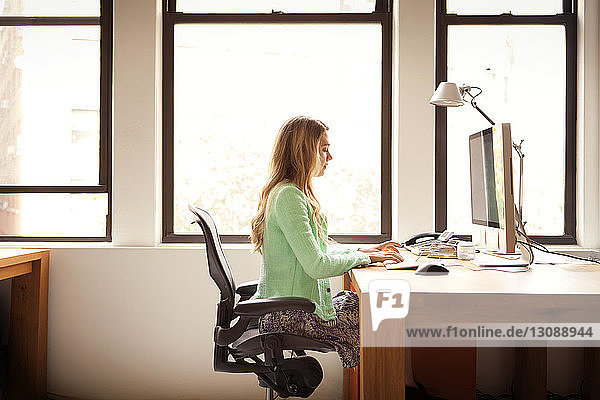 Side view of businesswoman using computer at office desk
