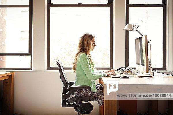 Seitenansicht einer Geschäftsfrau  die einen Computer am Büroschreibtisch benutzt