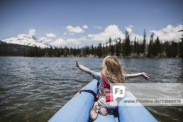 Rear view of carefree girl with arms outstretched sitting in inflatable raft on lake