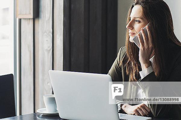 Geschäftsfrau benutzt Smartphone und schaut im Café weg