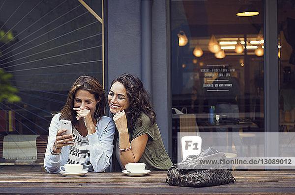Glückliche reife Frauen mit Smartphone im Straßencafé