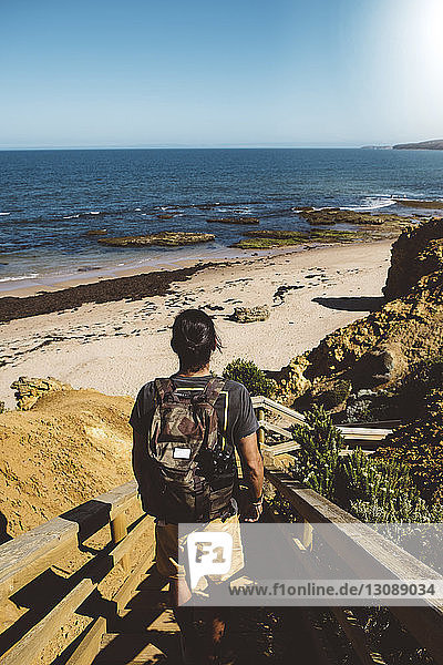 Rear view of man with backpack standing on steps at beach against clear blue sky during sunny day