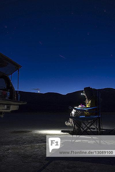 Wanderin  die nachts eine Stirnlampe benutzt  während sie auf einem Campingstuhl sitzt