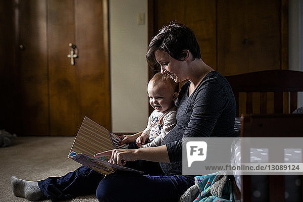Pregnant woman showing picture book to daughter while sitting at home