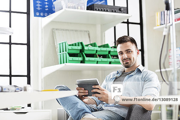 Portrait of confident engineer using tablet computer while sitting in electronics industry