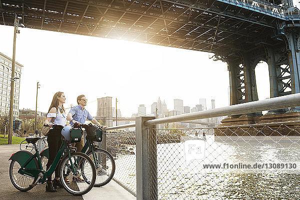Paar mit Fahrrädern steht an der Promenade am East River vor der Manhattan-Brücke