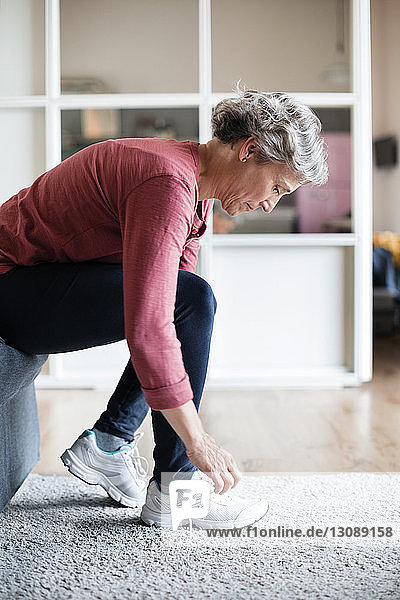 Side view of mature woman tying shoelace at home