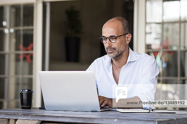 Businessman using laptop while sitting at table in office