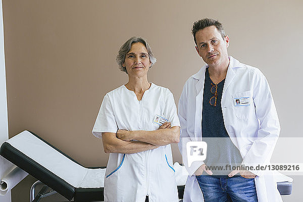 Portrait of confident doctors standing against wall at hospital