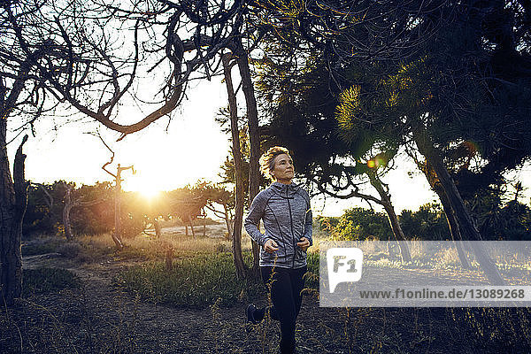 Woman jogging on field by trees during sunrise