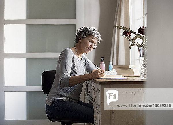 Mature woman writing in book on table at home