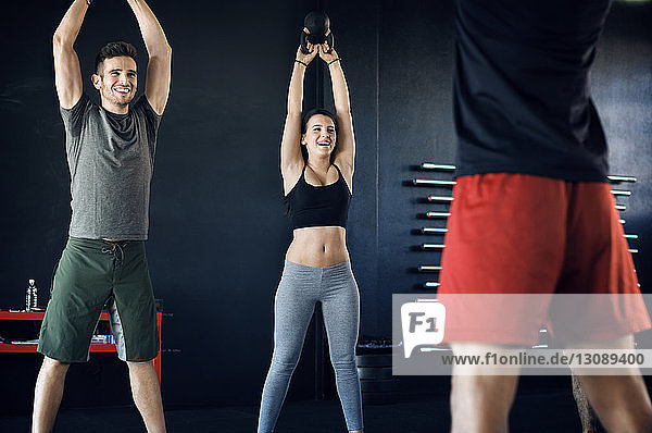 Happy athletes looking at instructor while lifting kettlebells in gym