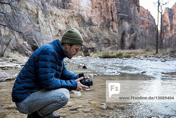 Seitenansicht eines Mannes mit Kamera  der am Bach vor Felsformationen kauert
