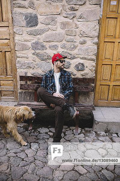 Mann in voller Länge auf Bank sitzend mit Hund am Gehsteig