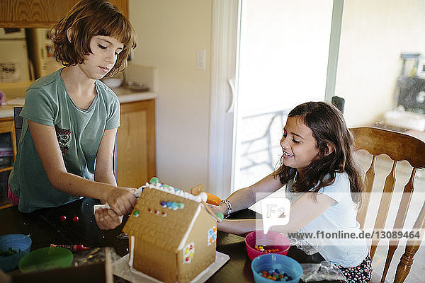 Sisters making gingerbread house at home