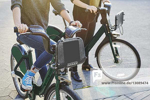Niedriger Anteil von Freundinnen mit Fahrrädern  die auf der Straße in der Stadt stehen