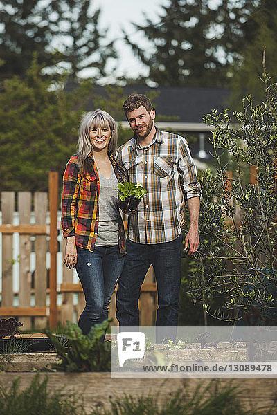Porträt eines lächelnden Paares mit Pflanzen im Hinterhof