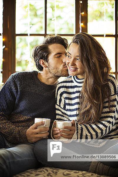 Mann küsst Freundin beim Kaffee trinken auf einem Fensterplatz in einer Nische zu Hause