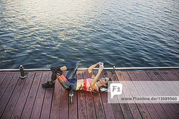 High angle view of woman lying and using smart phone on wooden walkway by river