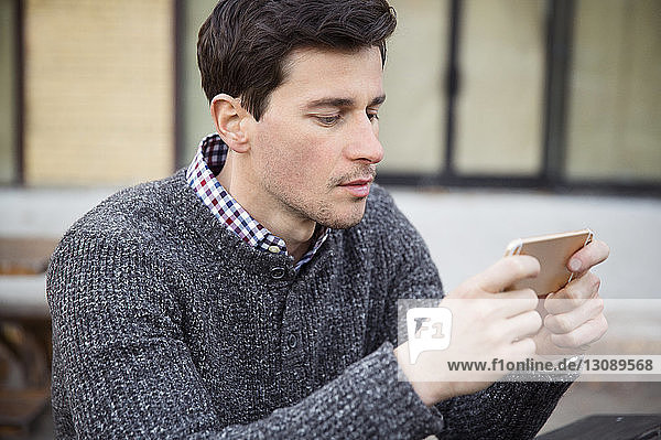 Man using mobile phone while sitting outdoors