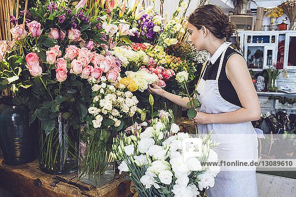 Female florist arranging roses in shop