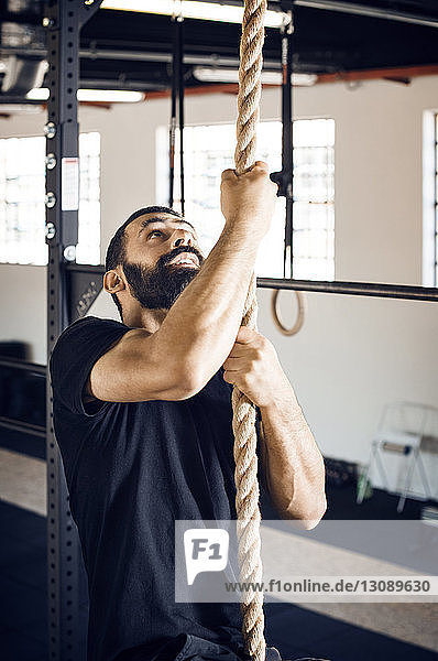 Determined male athlete climbing rope in gym