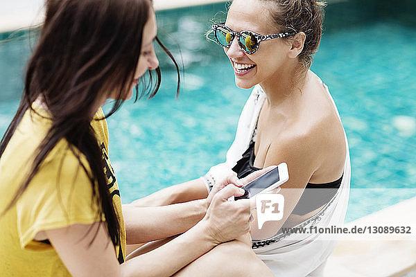Glückliche Frau benutzt Smartphone  während sie sich mit einem Freund am Pool entspannt