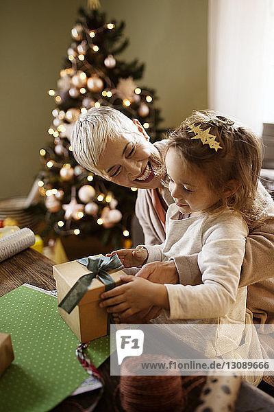 Glückliche Großmutter schaut auf ein Mädchen  das am Tisch ein Geschenk verpackt