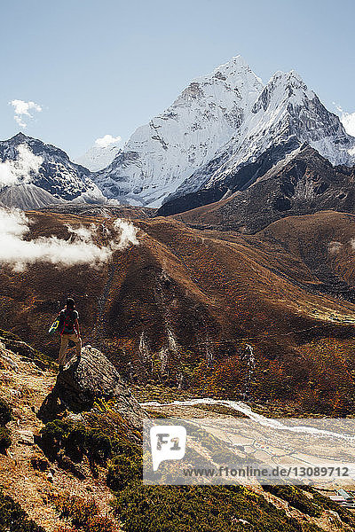 Rear view of male hiker standing on rock against blue sky at Sagarmatha National Park during sunny day