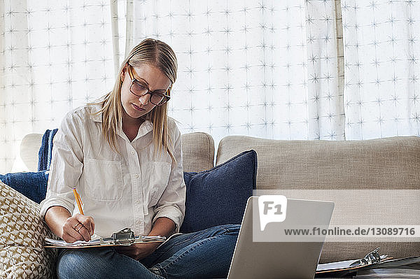 Woman writing on clipboard while sitting with laptop on sofa at home