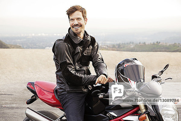 Cheerful biker sitting on motorcycle at countryside