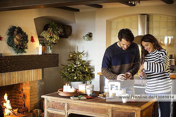 Lächelndes Paar schmückt zu Weihnachten sein Zuhause