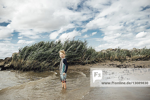 Portrait of boy standing at beach against cloudy sky