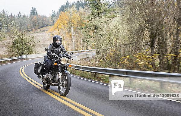 Weibliche Motorradfahrerin mit Sturzhelm beim Motorradfahren auf der Landstraße