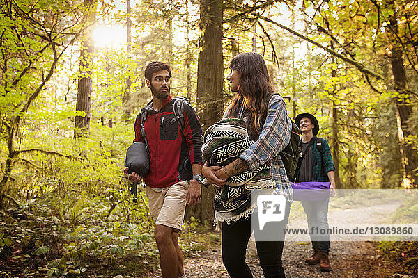 Friends talking while walking in forest